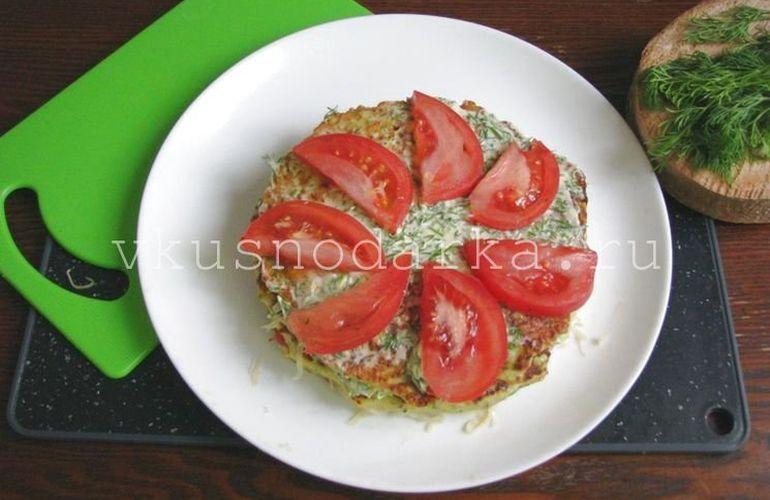 Сверху на соус выложить нарезанные на кусочки помидоры